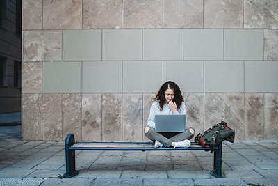 Young woman using laptop on the bench - p1166m2095025 by Cavan Images
