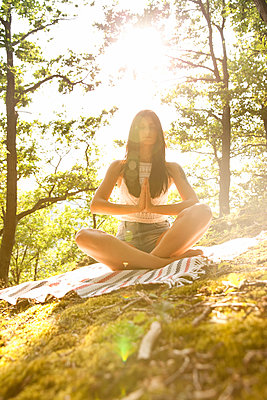 Young woman sitting on blanket in forest practicing yoga - p300m2012878 by Michelle Fraikin