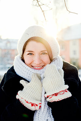 Sweden, Stockholm, Portrait of young woman wearing knit hat and gloves - p352m1126791f by Anna Larsson