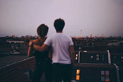 Rear view of couple looking at city while standing on terrace during dusk against sky - p426m2159168 by Maskot