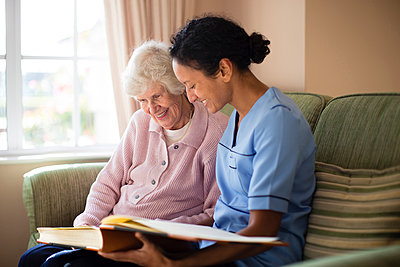 Nurse and patient looking at photo album - p555m1305760 by Resolution Productions