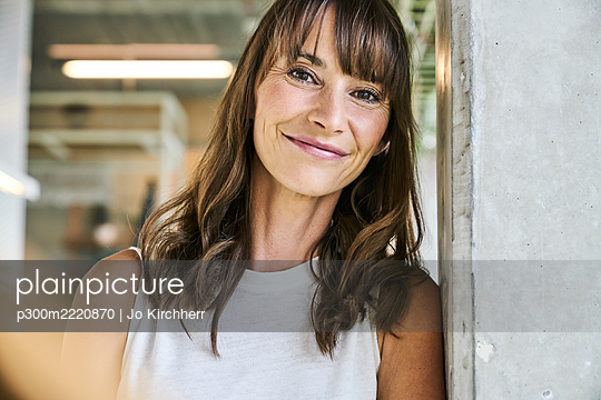 Beautiful woman smiling while leaning on wall at home - p300m2220870 by Jo Kirchherr