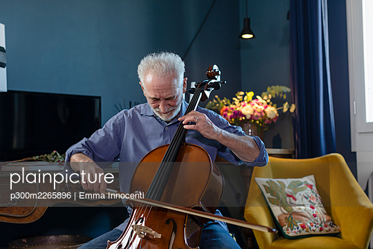 Senior man playing cello while sitting in living room at home - p300m2265896 by Emma Innocenti