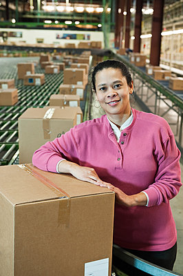 Portrait of an African American female warehouse worker in a large distribution warehouse with products stored in cardboard boxes. - p1100m1575505 by Mint Images