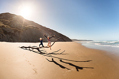 Two happy children jumping from driftwood at a beach - p1166m2137082 by Cavan Images
