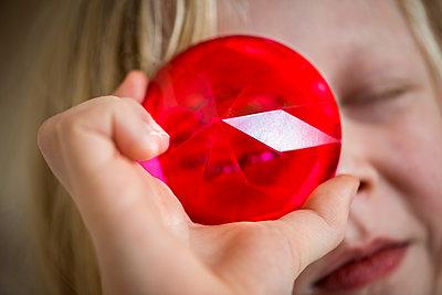 Little boy looking though red prism - p1418m2262403 by Jan Håkan Dahlström