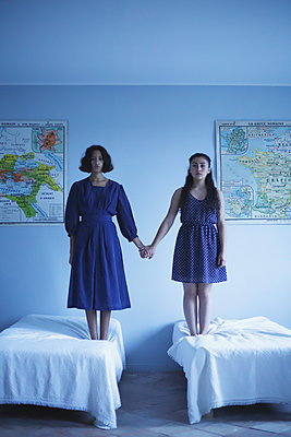 Two women holding hands and standing on bed - p1521m2129135 by Charlotte Zobel