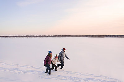 Family holding hands while walking on snow against sky during winter - p300m2265149 by Ekaterina Yakunina