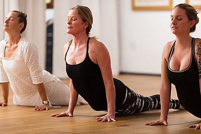 Three Women In Upward-facing Dog Yoga Pose In An Art Gallery - p343m1223770 by Robert Benson