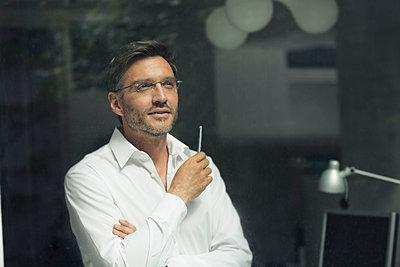 Portrait of businessman standing gazing out of office window - p429m1133618f by Philipp Nemenz