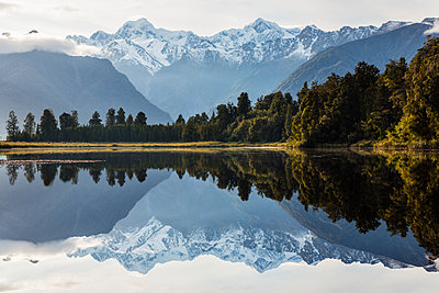 Mountains and forest reflecting in still lake, Fox Glacier, South Westland, New Zealand - p555m1410103 by Jeremy Woodhouse