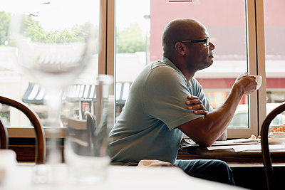 African American man drinking coffee in restaurant - p555m1479937 by Mark Edward Atkinson/Tracey Lee