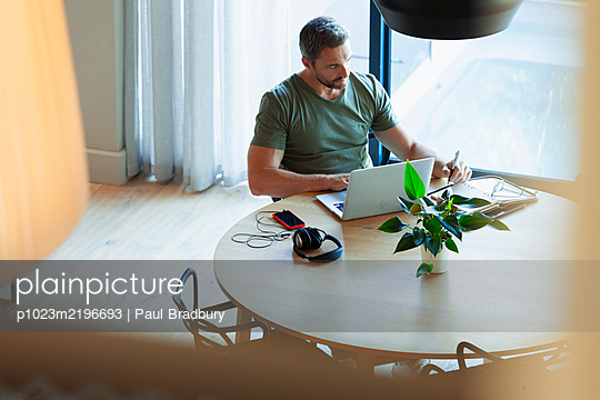 Man using laptop, working from home at dining table - p1023m2196693 by Paul Bradbury