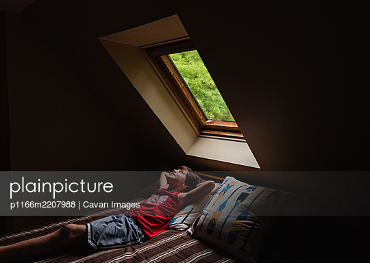 Young boy laying on bed looking up through a sky light in a dark room. - p1166m2207988 by Cavan Images