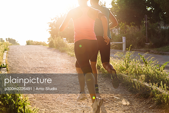 Fit heterosexual couple jogging in park during sunset - p300m2226491 by Arno Studio