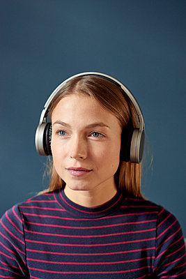 Young woman listens to music with headphones - p1124m1589226 by Willing-Holtz