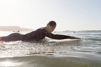 Side view portrait of happy male surfer lying on surfboard in sea during sunset - p1166m1414553 by Cavan Images