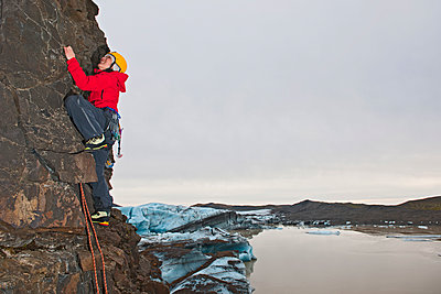 female climber scaling step rock face in Skaftafell / Iceland - p1166m2268509 by Cavan Images