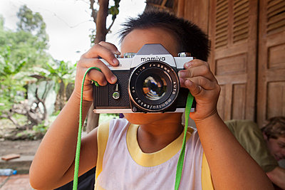 Kid shooting with an old film mamiya camera in Go Dau, Tay Ninh Province, Vietnam, Asia. - p934m832577 by Yan Lerval photography