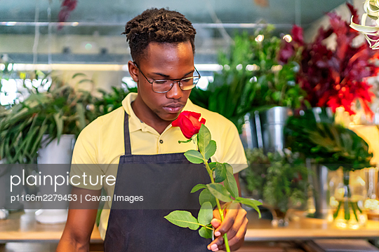 young african entrepreneur smelling the flowers of his business - p1166m2279453 by Cavan Images