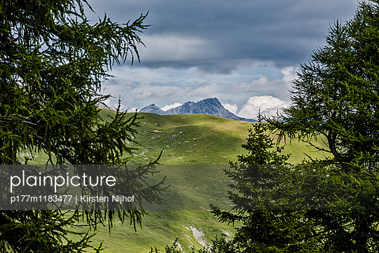 Bergspitze am Horizont mit Bäumen und Wiese - p177m1183477 von Kirsten Nijhof