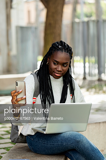 Female student using laptop and cell phone on a bench - p300m2167563 by Valentina Barreto