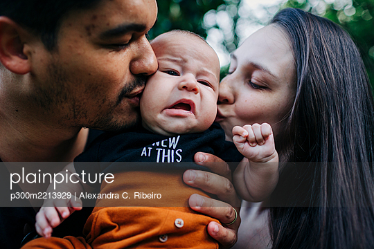 Young parents kissing cute baby boy - p300m2213929 by Alexandra C. Ribeiro