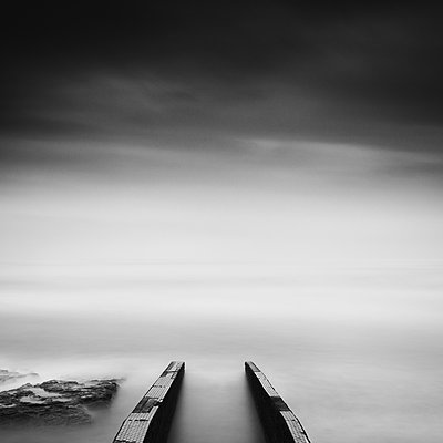 Long exposure of pier in the sea and dramatic sky in Inamuragasaki - p1166m2078134 by Cavan Images