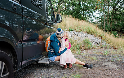 mother and daughter hugging outside a camper van whilst camping - p1166m2137067 by Cavan Images
