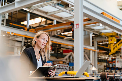 Female entrepreneur looking away while holding diary sitting in industry - p300m2240079 by Daniel Ingold