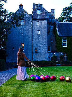 Woman pulls metallic baubles across lawn, Scotland, UK - p349m2167725 by Polly Wreford
