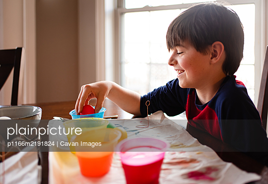 Happy boy dipping an egg into a bowl of dye to color it for Easter. - p1166m2191824 by Cavan Images