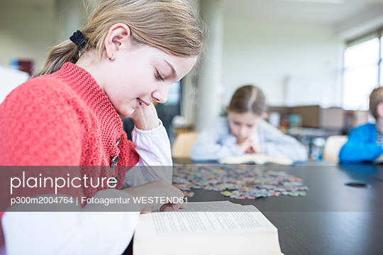 Schoolgirl reading book on table in school break room - p300m2004764 von Fotoagentur WESTEND61