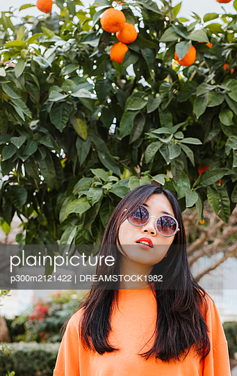 Portrait of young asian woman, tangerine tree in the background - p300m2121422 by DREAMSTOCK1982