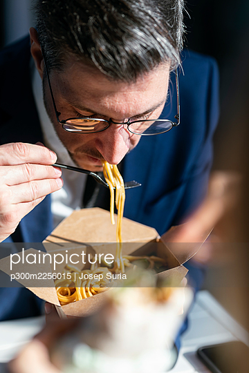 Businessman eating noodles while sitting in cafeteria at office - p300m2256015 by Josep Suria