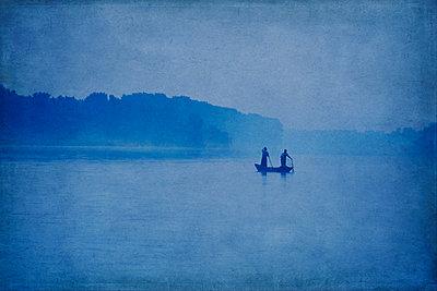 Fishermen in boat shrouded in mist - p1312m1191078 by Axel Killian