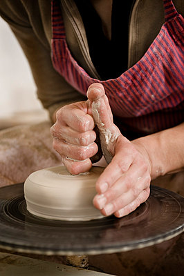 Germany, Bavaria, Mid adult woman working with clay on potter's wheel - p300m879251 by Robert Niedring