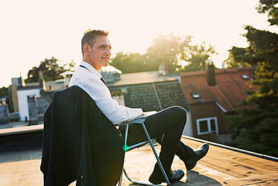 Businessman relaxing on roof - p341m2008650 by Mikesch