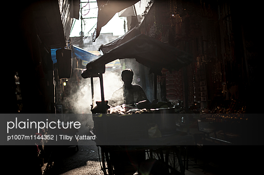 Street seller in light shadow and smoke - p1007m1144352 by Tilby Vattard