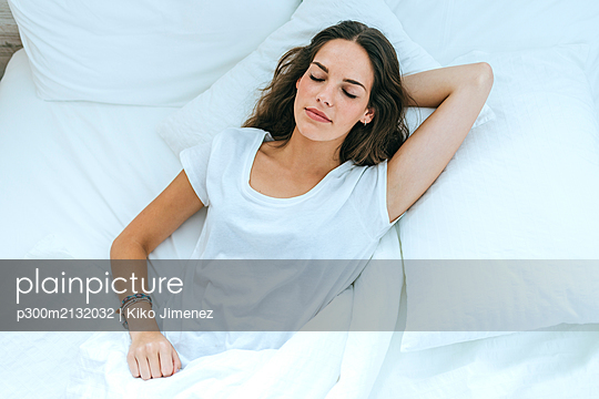 Young woman sleeping in bed at home - p300m2132032 von Kiko Jimenez