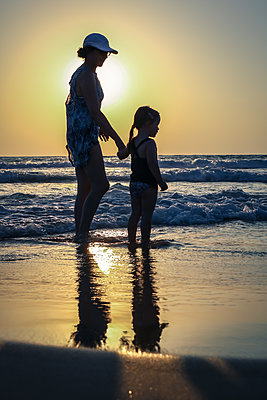 Mother and Child on Beach at Sunset  - p1019m1467946 by Stephen Carroll