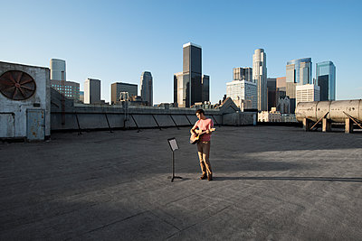 A man standing on a rooftop overlooking the city playing a guitar. - p1100m1107171 by Mint Images