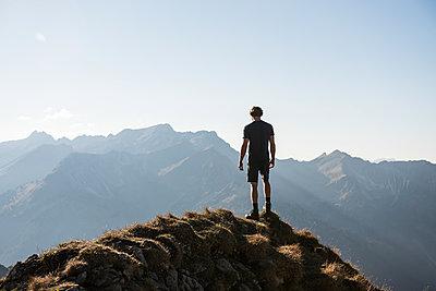 Junger Wanderer genießt die Aussicht  - p1142m2056558 von Frithjof Kjer