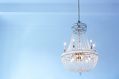 Lighted old ceiling lamp in front of light blue wall - p300m1029063f by Dieter Schewig