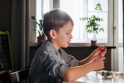 Boy assembling robot at home - p300m2170773 by Ekaterina Yakunina