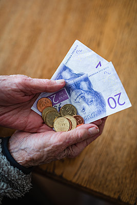 Hands holding banknotes and coins - p312m2139394 by Anna Johnsson