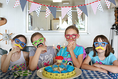 Children wearing disguises at birthday party - p555m1408736 by Shestock
