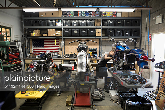 Female motorcycle mechanics fixing motorcycles in auto repair shop