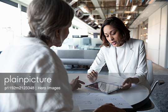 Financial advisor discussing with senior client with digital tablet - p1192m2123348 by Hero Images