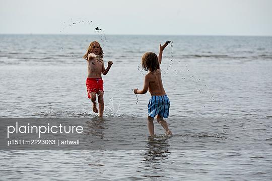 Zwei Kinder spielen im flachen Wasser - p1511m2223063 von artwall